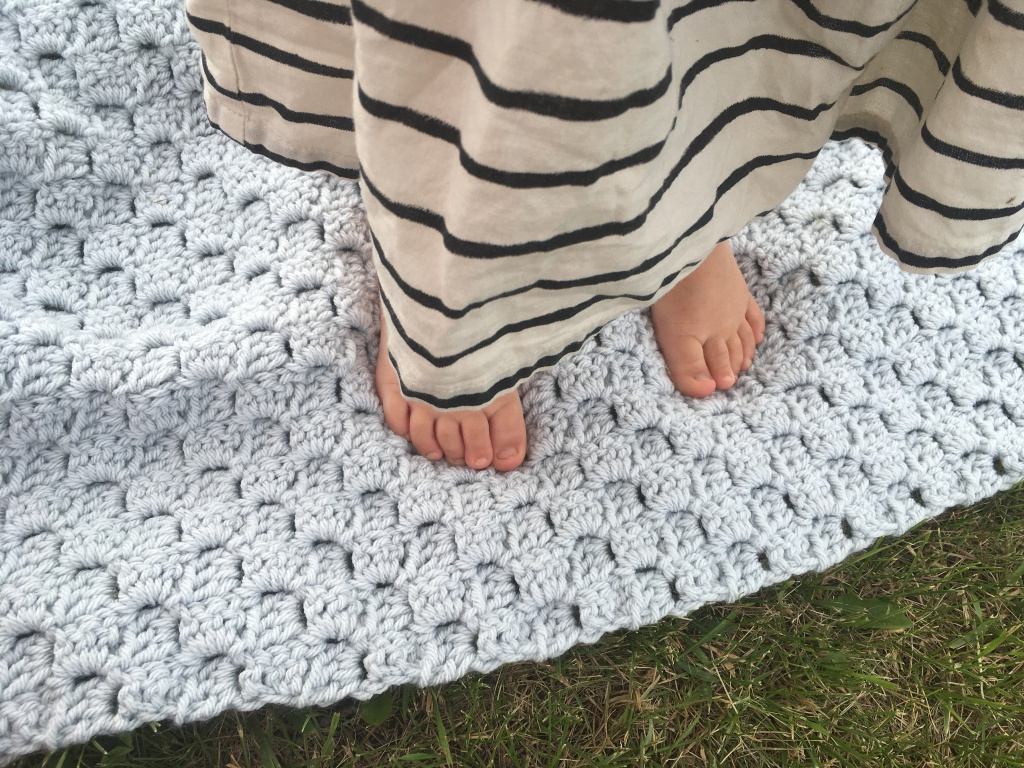 A round toddler visible from about the knees down stands barefoot on the Bandit stroller blanket on the grass.  Part of her feet are just visible from under the off-white skirt with black stripes.