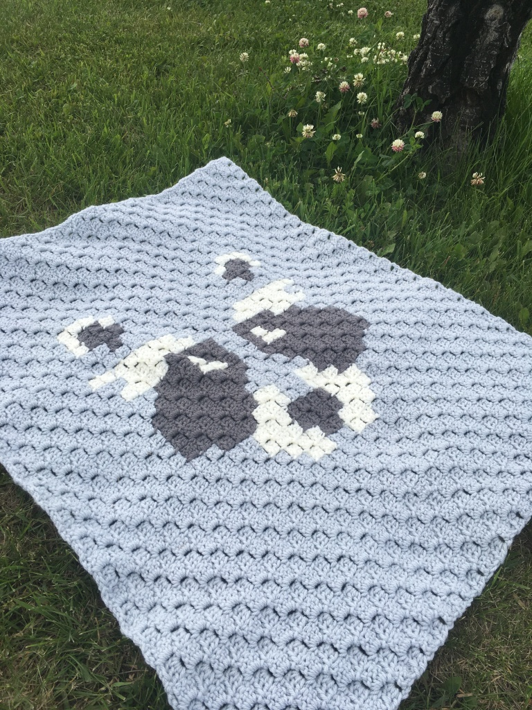 The Bandit stroller blanket lays spread on the grass. It is shades of grey and white with a raccoon face in the middle.