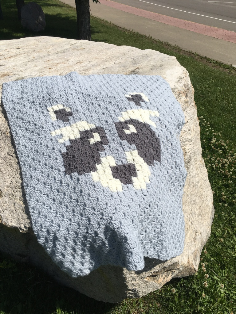 The Bandit stroller blanket is draped on a very large rock.