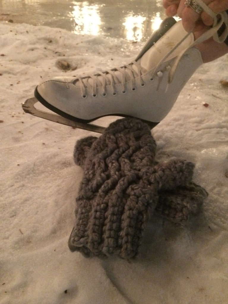 The Sparks Fly Mitts lay in the snow beside Meggie's skate as she laces it up by the ice.