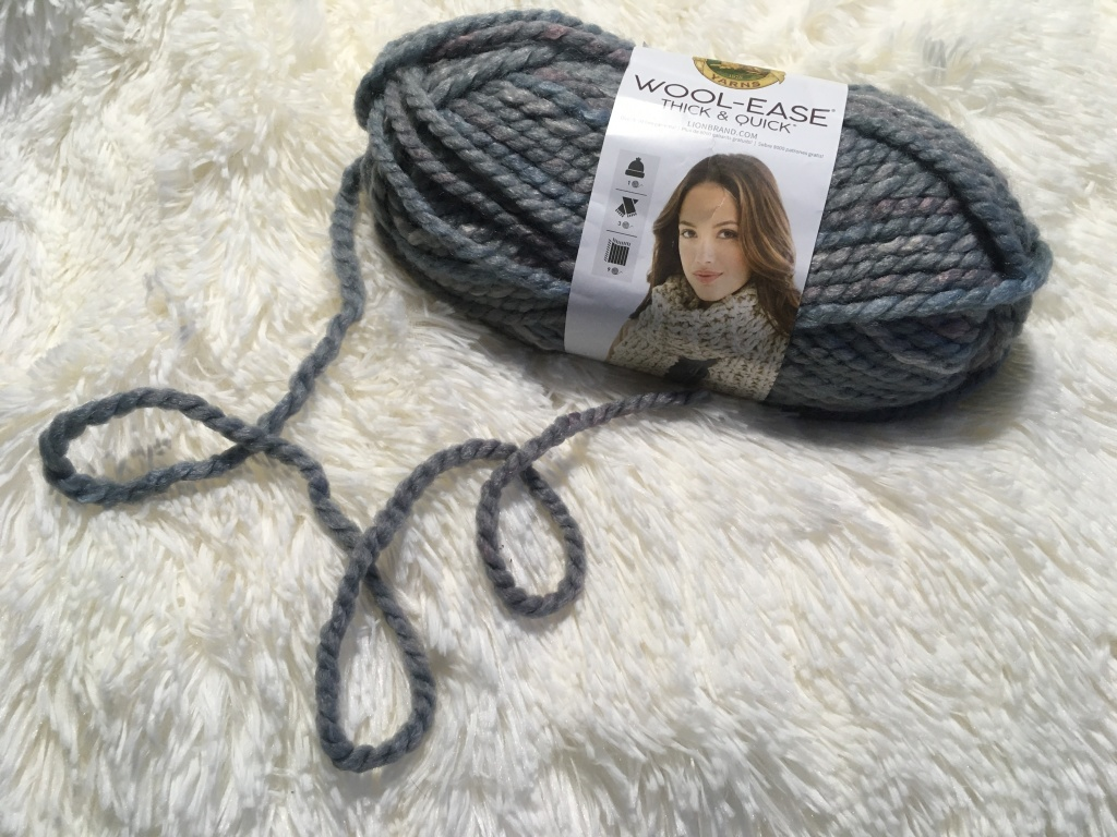 a partly used skein of grey yarn sits on a white fluffy blanket. The free end loops and twirls on the blanket a few times.
